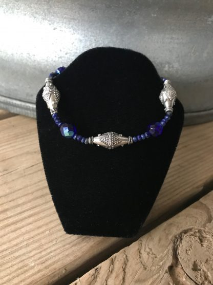 Cobalt Blue Faceted Czech Glass With Aurora Borealis Finish, Microfaceted Lapis Lazuli Rondelles, and Silver Bali Bicones Bracelet hanging from a black velveteen bracelet display resting on weathered 2x6 deck boards in front of a silver metal stock tank.