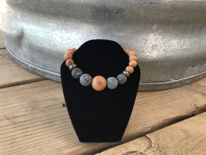 Unfinished Bayong Wood Rounds, Natural Lava Rock Rounds, and Dakota Stones Pyrite Rondelles Scentable hanging from a black velveteen bracelet display resting on weathered 2x6 deck boards in front of a silver metal stock tank.