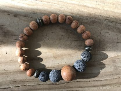 Unfinished Bayong Wood Rounds, Natural Lava Rock Rounds, and Dakota Stones Pyrite Rondelles Scentable Bracelet lying on weathered 2x6 deck boards.