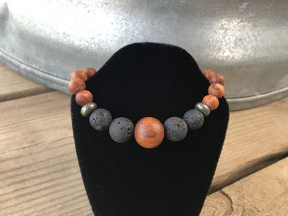 Oiled Bayong Wood Rounds, Natural Lava Rock Rounds, and Dakota Stones Pyrite Rondelles Scentable Bracelet hanging from a black velveteen bracelet display resting on weathered 2x6 deck boards in front of a silver metal stock tank.