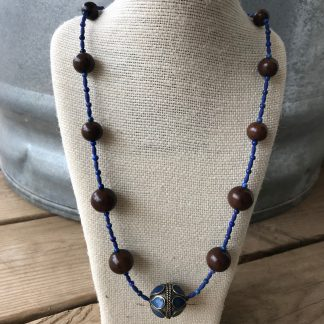 Lapis-Style Afghani Stone Rice Beads, Lapis Lazuli Rounds, Graduated Magkuno Wood Rounds, and Lapis-Inlaid Afghan Tribal Silver Bead Necklace hanging from a textured hemp necklace display resting on weathered 2x6 deck boards in front of a silver metal stock tank.