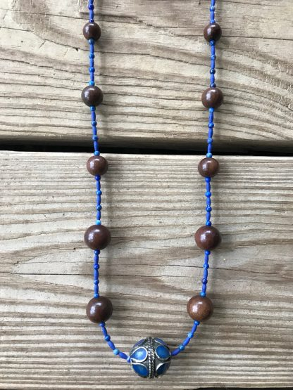 Lapis-Style Afghani Stone Rice Beads, Lapis Lazuli Rounds, Graduated Magkuno Wood Rounds, and Lapis-Inlaid Afghan Tribal Silver Bead Necklace lying on weathered 2x6 deck boards. A closer view of the focal bead.