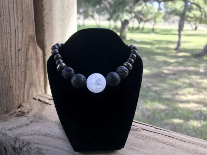 Raw White Quartz Focal, Lava Rounds, Pyrite Rondelles, and Unfinished Ebony Rounds Scentable Bracelet hanging from a black velveteen necklace display resting on a wood porch rail.