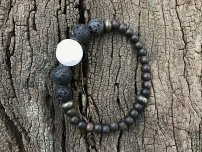 Raw White Quartz Focal, Lava Rounds, Pyrite Rondelles, and Unfinished Ebony Rounds Scentable Bracelet resting on a wood log.