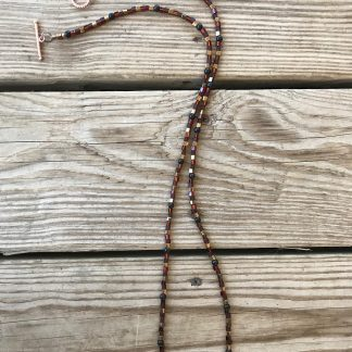 Miyuki Silver-lined Dark Amber, Transparent Frosted Dark Amber, and Opaque Metallic Dark Gold Glass Cubes, Tiger Ebony Rounds, and Copper Coin Focals Necklace lying on weathered 2x6 deck boards.