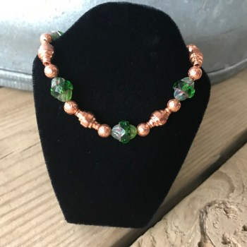 Green Picasso Czech Glass Beads Peridot Turbines, Copper Drums, and Hammered Copper Rounds Bracelet hangs hanging from a black velveteen bracelet display resting on weathered 2×6 deck boards in front of a silver metal stock tank.