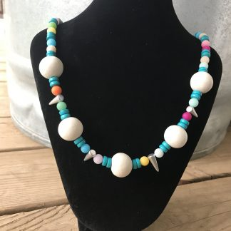 Bleached Whitewood, Candy Mountain Jade, Turquoise Wood, and Silver Cones Necklace on a black velveteen necklace display. The display rests on weathered 2×6 deck boards and sits in front of a silver metal stock tank.