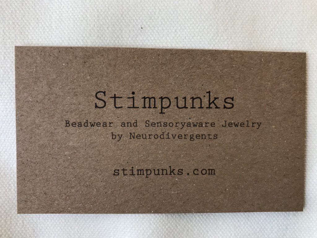 "Stimpunks business card printed on brown kraft paper lying on a white canvas background. Line 1 of text reads: ""Stimpunks"". Line 2 reads: ""Beadwear and Sensoryaware Jewelry by Neurodivergents"". Line 3: stimpunks.com."