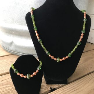 Custom for LM: Green Picasso Czech Glass Peridot Turbines, Copper Drums, Hammered Copper Rounds, and Microfaceted Peridot Bracelet and Necklace Set hanging from black velveteen necklace displays resting on weathered 2x6 deck boards in front of a silver metal stock tank.