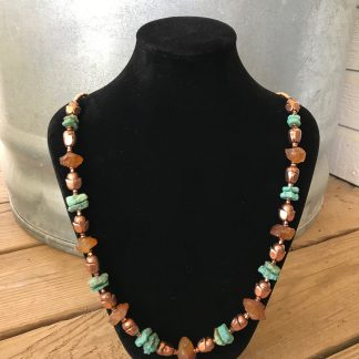 Marigold Quartz Matte Hammered Disc Nuggets, Raw Turquoise Rondelles, Copper Flower Buds, and Copper Rounds Necklace hanging from a black velveteen necklace display resting on weathered 2x6 deck boards in front of a silver metal stock tank.