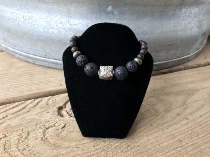 Lava Rounds, Pyrite Rondelles, and Unfinished Ebony Rounds Scentable Bracelet with Karen Hill Tribe Silver Cushion Focal hanging from a black velveteen bracelet display resting on weathered 2x6 deck boards in front of a silver metal stock tank.