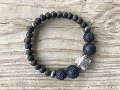 Lava Rounds, Pyrite Rondelles, and Unfinished Ebony Rounds Scentable Bracelet with Karen Hill Tribe Silver Cushion Focal lying on weathered 2x6 deck boards.