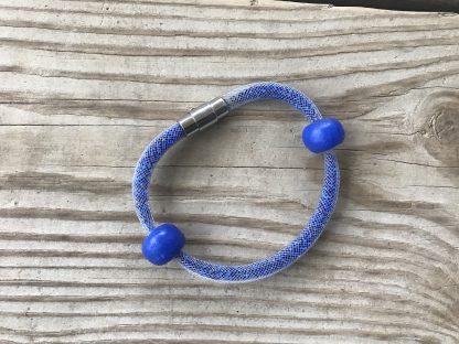 Sapphire Blue Mesh Shake Bracelet lying on weathered 2x6 deck boards.