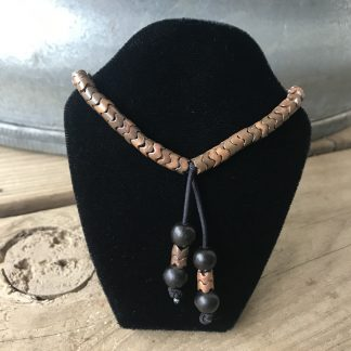 Copper Interlocking Snake Bracelet hanging from a black velveteen bracelet display resting on weathered 2x6 deck boards in front of a silver metal stock tank.