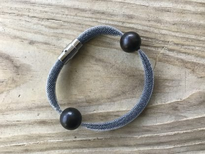 Onyx Black Mesh Shake Bracelet lying on weathered 2x6 deck boards.