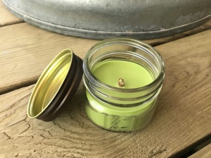 Green Apple Scented Candle with Wooden Tube Wick Green Apple Scented Candle with Wooden Tube Wick resting on weathered 2x6 deck boards in front of a silver metal stock tank.