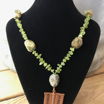 Rainforest Jasper Nuggets, Peridot Chips, and Toho Silver-lined Peridot Green Seed Beads Necklace with Copper Lattice Rectangular Baule Pendant hanging from a black velveteen bracelet display resting on weathered 2x6 deck boards in front of a silver metal stock tank.