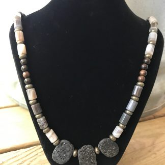 Botswana Agate Drums, Ebony Wood Rounds, Pyrite Rondelles, and Lava Ovals Scentable Necklace hanging from a black velveteen necklace display resting on weathered 2x6 deck boards in front of a silver metal stock tank.