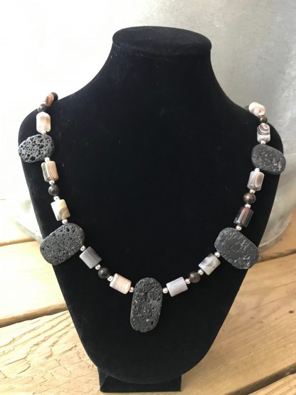 Botswana Agate Drums, Ebony Wood Rounds, Silver Rounds, and Lava Ovals Scentable Necklace hanging from a black velveteen bracelet display resting on weathered 2x6 deck boards in front of a silver metal stock tank.