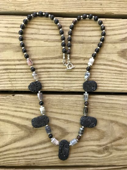 Botswana Agate Drums, Ebony Wood Rounds, Silver Rounds, and Lava Ovals Scentable Necklace lying on weathered 2x6 deck boards.