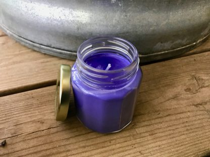 Bluebonnet Scented Candle in 6.5oz Jar with Gold Metal Twist Lid resting on weathered 2x6 deck boards in front of a silver metal stock tank.