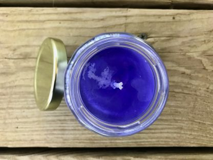 Bluebonnet Scented Candle in 6.5oz Jar with Gold Metal Twist Lid lying on weathered 2x6 deck boards.