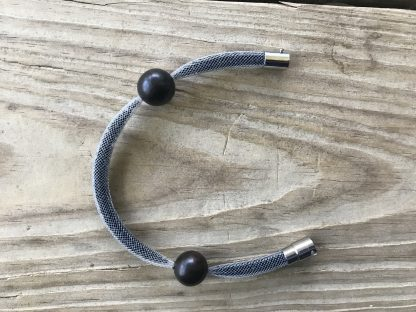 Onyx Black Mesh Shake Bracelet lying on weathered 2x6 deck boards with clasp opened.