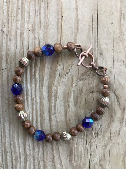 Cobalt Blue Faceted Czech Glass With Aurora Borealis Finish, Madre de Cacao Wood, and Corrugated Brass Bicones Bracelet lying on weathered 2x6 deck boards.
